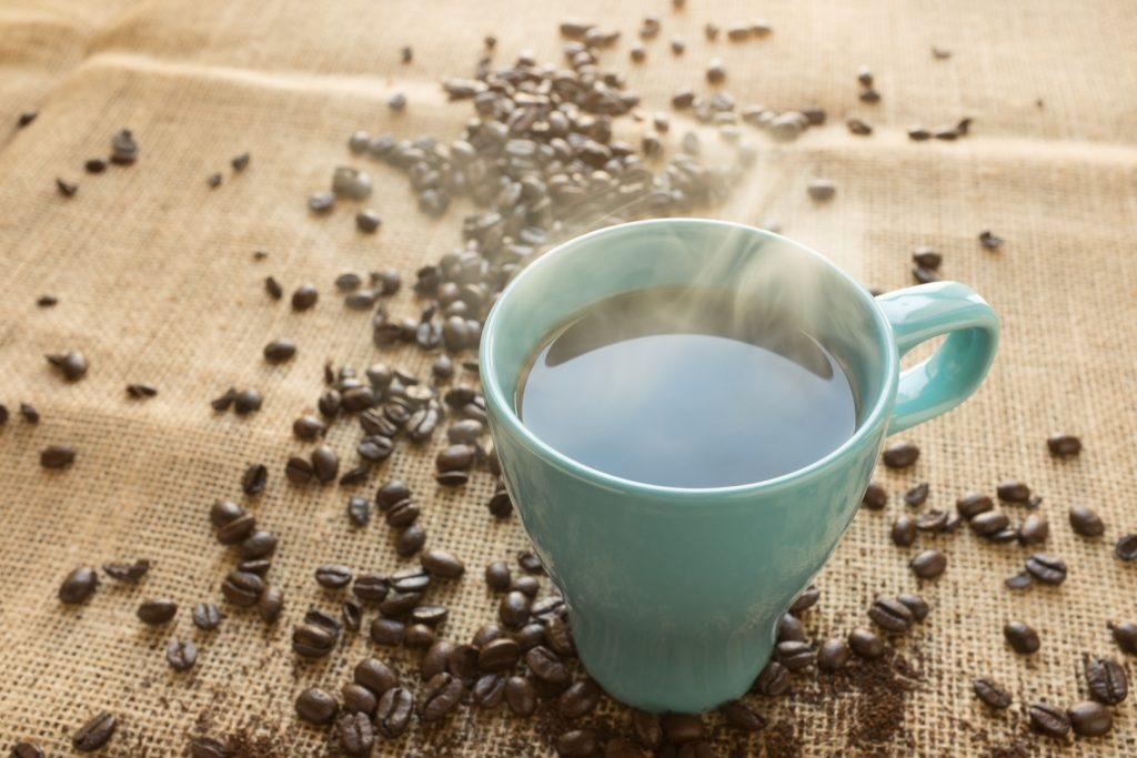 Tazza di caffe con manciata di chicchi